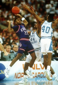 30 MAR 1991: Kansas University guard Sean Tunstall (22) and North Carolina forward Rick Fox (44) and guard Hubert Davis (40) reach for the loose ball during the NCAA National Basketball Championship semifinal game at the Hoosier Dome in Indianapolis, IN. Kansas defeated North Carolina 79-73. Rich Clarkson/NCAA Photos.