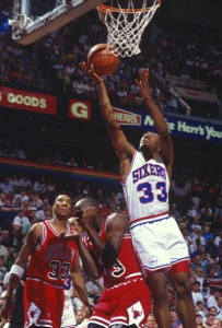 PHILADELPHIA, PA - CIRCA 1990: Hersey Hawkins #33 of the Philadelphia 76ers lays the ball up over Michael Jordan #23 of the Chicago Bulls during an NBA basketball game circa 1990 at The Spectrum in Philadelphia, Pennsylvania. Hawkins played for the 76ers from 1988-93. (Photo by Focus on Sport/Getty Images)